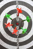 Dartboard with red and green darts — Stock Photo
