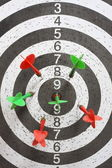 Six red and green darts on game board — Stockfoto