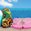 Closeup beach with sandals towel and suntan lotion — Stock Photo