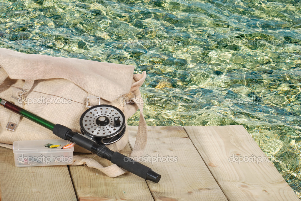 Fly fishing equipment on a dock with rippled water  — Stock Photo #4174985