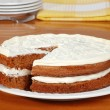 Sliced carrot cake with plates and yellow napkin — Stock Photo