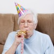 Senior woman with birthday hat blowing a noise maker — Stock Photo