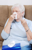 Sick senior with thermometer blowing her nose — Stock Photo