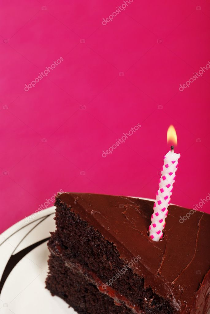 Closeup of slice of birthday cake with copy space focus on wick with pink background  — Lizenzfreies Foto #4267313