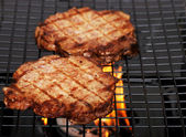 Two barbecue hamburgers with flames — Stock Photo