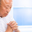 Praying senior asian in hospital — Stock Photo