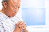Praying senior asian in hospital — Stock Photo