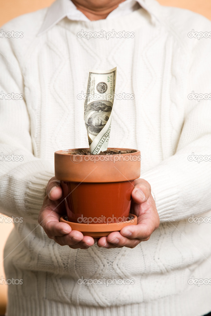 A shot of a businessman holding a pot with money planted, can be used for financial or investment or savings concept — Stock Photo #5453106