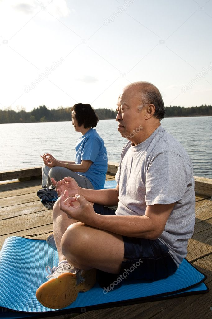 A shot of a senior asian couple meditating and practicing yoga — Stockfoto #5453284