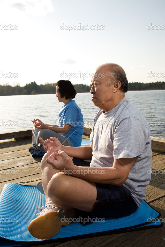 A shot of a senior asian couple meditating and practicing yoga — Stock fotografie #5453284