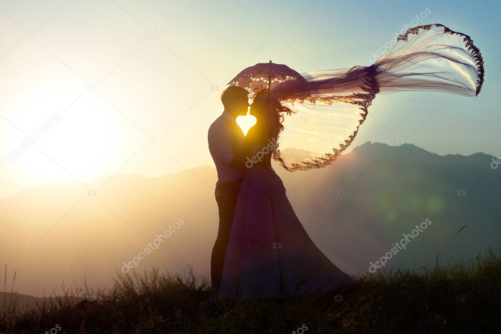 The groom and the bride kiss in mountains against a decline.   #5167334