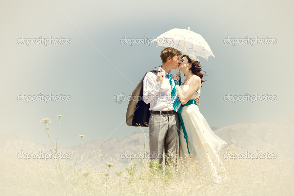 The groom and the bride kiss under summer the hot sun in mountains. — Stock Photo #5167337