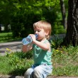 Stock Photo: Thirsty boy drinking water outdoors