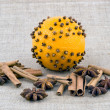 Christmas decoration - orange with cloves on linen background - Stock Photo