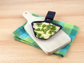 Raclette pan with cheese and spring onion - party food — Stock Photo