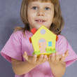 The little girl with a small paper house in hands - Stock Photo