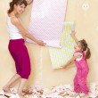 Mom and daughter try on wallpaper — Stock Photo