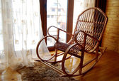 Wooden rocking-chair at a window — Stock Photo
