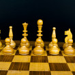 Woody board with black and white chess figures — Stock Photo
