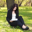 The businesswoman sitting on a grass, reading a book — Stock Photo