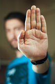 Young man gesturing stop with his hand — Stock Photo