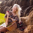 Beautiful blonde smiling woman with apple on hay stack at farm — Stockfoto