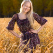 Beautiful blonde woman in dress smilling at the wheat field — Stock Photo