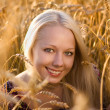 Beautiful blonde woman smilling at the wheat field closeup — Stock Photo