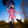 Young beautiful smiling woman jump outdoor with umbrella in hand — Stock Photo #4066144