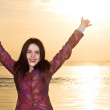 Portrait of happy smilling woman hands up on sunset river backgr — Stock Photo