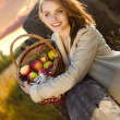 Young woman smile at farm with many apple in basket - Stock Photo