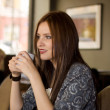 Stock Photo: Beautiful young girl sipping coffee