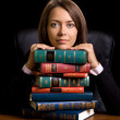 Young woman with many book at the desk on black background — Stock Photo