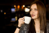 Beautiful young girl sipping coffee — Stock Photo