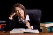 Jeune femme avec livre au bureau sur fond noir — Photo