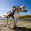 Young cowgirl on white horse at the rural river — Stock Photo