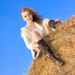 Beautiful happy woman siting on haystack under blue heaven — Stock Photo