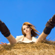 Beautiful woman siting on haystack under blue heaven - Stock Photo