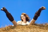 Beautiful woman siting on haystack under blue heaven — Stock Photo