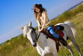 Young cowgirl on white horse — Stok fotoğraf