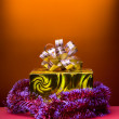 Cristmas gift golden box on orange background - Stock Photo