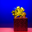 cristmas gift red magic box with golden bow on blue background — Stock Photo