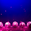 Five purple disco balls reflectoin lights on blue background - Stock Photo