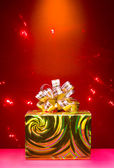 Cristmas gift golden box on red magic background — Stock Photo