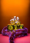 Cristmas gift golden box on orange background — Stock Photo