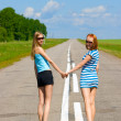 Two young women walking on the road countryside — Stok fotoğraf