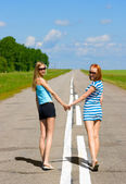 Two young women walking on the road countryside — Stock Photo