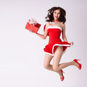 Smiling woman in red xmas sexy costume fly with gift — Stock Photo