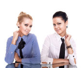 Two businesswoman siting on reflection table isolated on white — Stock Photo