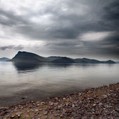 Storm clouds over the island in sea — Foto Stock
